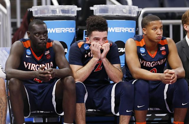 <p>Virginia forward London Perrantes, center, guard Marial Shayok, left, and guard Devon Hall watch from the bench during the final seconds of a second-round game of the NCAA men's college basketball tournament against Florida, Saturday, March 18, 2017, in Orlando, Fla. Florida defeated Virginia 65-39. (AP Photo/Wilfredo Lee) </p>