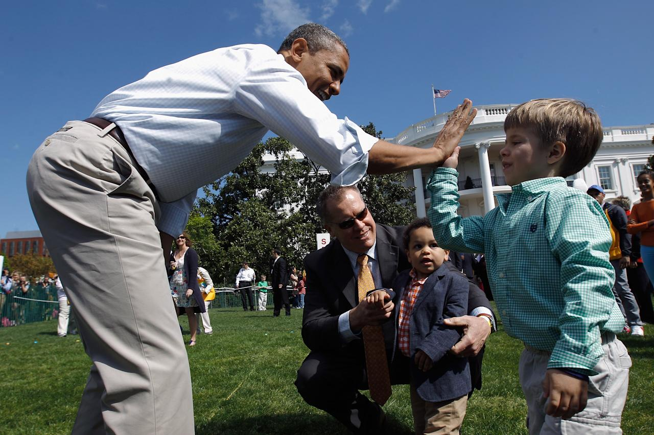 U.S. President Barack Obama (L) engages a young participant during the White House Easter Egg Roll on the South Lawn of the White House on April 9, 2012 in Washington, DC. Thousands of people people are expected to attend the 134-year-old tradition of rolling colored eggs down the White House lawn that was started by President Rutherford B. Hayes in 1878.  (Photo by Chip Somodevilla/Getty Images)