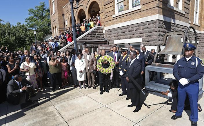 Churchgoers file outside the church as a wreath is carried at the 16th Street Baptist Church in Birmingham, Ala., Sunday, Sept. 15, 2013. The congregation gathered outside the church for the wreath laying ceremony at the spot where a bomb was detonated 50 years ago by the Ku Klux Klan, killing four young girls. (AP Photo/Hal Yeager)