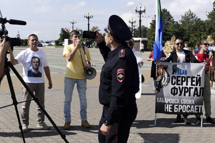 A police officer looks at a group of demonstrators in Khabarovsk, Russia, who had gathered in support of Sergei Furgal, the former governor of the region in the country's Far East, on Saturday, Sept. 11, 2021. A few demonstrators gather in a persistent reminder of the larger protests last year demanding the release of the region's former governor, Sergei Furgal. (AP Photo/Sergei Demidov)