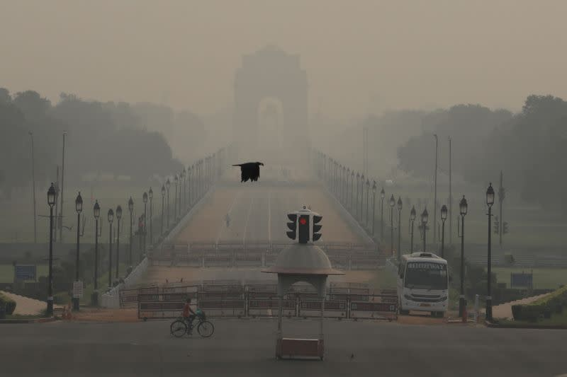 A man rides a bicycle on a hazy morning near India Gate, in New Delhi