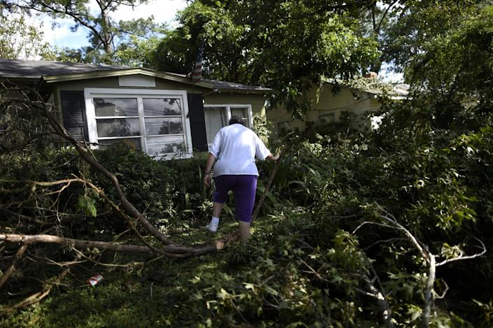 Carol Briggs, 70, walks over downed tree limbs while returning home for the first time after Hurricane Irma in Jacksonville, Florida, U.S. September 12, 2017. Picture taken September 12, 2017. REUTERS/Mark Makela