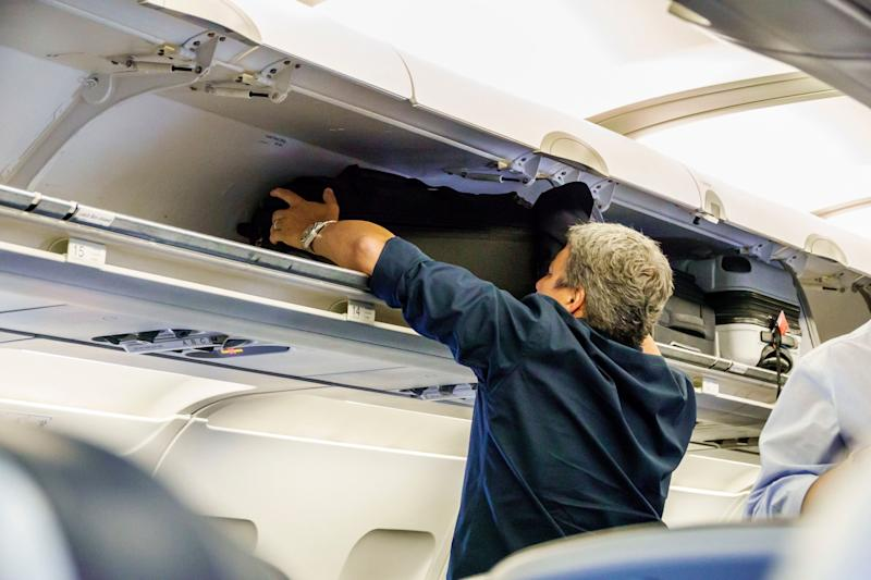 Florida, Miami International Airport, airplane cabin, open overhead luggage storage. (Photo by: Jeffrey Greenberg/UIG via Getty Images)