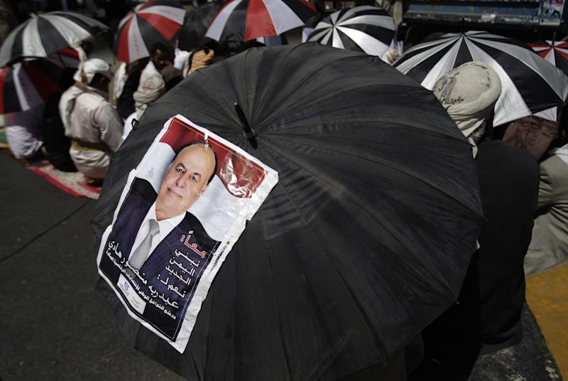 A man holds umbrella with a photograph of vice president Abed Rabbo Mansour Hadi during a pro-election rally in Sanaa, Yemen, Friday, Feb. 17, 2012.  Yemen will hold presidential elections according to the Gulf-brokered deal under which President Ali Abdullah Saleh who stepped down in exchange for immunity from prosecution. His vice president, Abed Rabbo Mansour Hadi,  is the only candidate in the balloting. (AP Photo/Hani Mohammed)