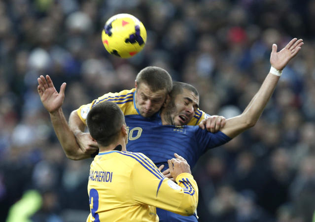 FILE - In this Nov. 19, 2013, file photo, Karim Benzema is blocked byUkraine's Vitalii Mandziuk, top, and Ukraine's Ukraine's Yevhen Khacheridi during the World Cup qualifying playoff second-leg soccer match between France and Ukraine at Stade de France stadium in Saint Denis, outside Paris. (AP Photo/Christophe Ena, File)