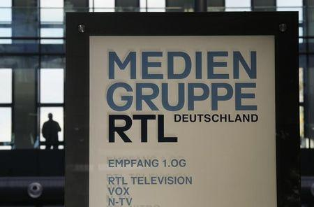 A man stands in a window of the headquarters of RTL Media Group Germany in Cologne