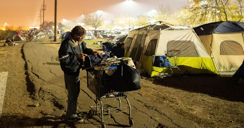 A man displaced by the Camp Fire, tends to his belongings at an evacuee encampment at a Walmart parking lot in Chico, California on November 19, 2018.