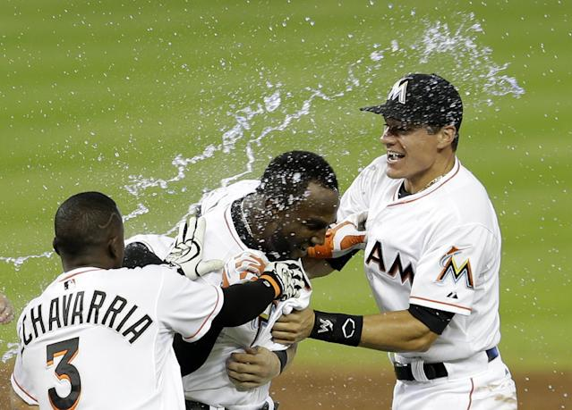 Miami Marlins' Marcell Ozuna, center, is congratulated by teammates Adeiny Hechavarria (3) and Derek Dietrich, right, after Ozuna hit a sacrifice fly driving in the game-wining run, 1-0, against the New York Mets in the ninth inning of a baseball game in Miami, Wednesday, May 7, 2014. (AP Photo/Alan Diaz)