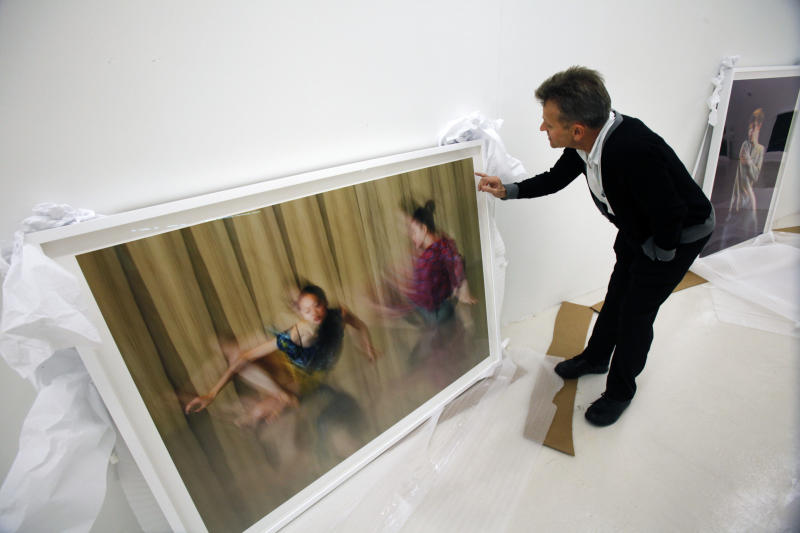 """In this Tuesday, Feb. 21, 2012 photo, dancer Mikhail Baryshnikov, talks about one of his photographs during an interview with The Associated Press, before the photos are hung at the Gary Nader Art Centre in Miami. The show, which opens Friday, Feb. 24, is titled """"Dance This Way"""" and features large-scale photographs of ethnic, hip-hop, ballet, modern and popular dances performed on stage by professionals and in nightclubs by amateurs. (AP Photo/Wilfredo Lee)"""