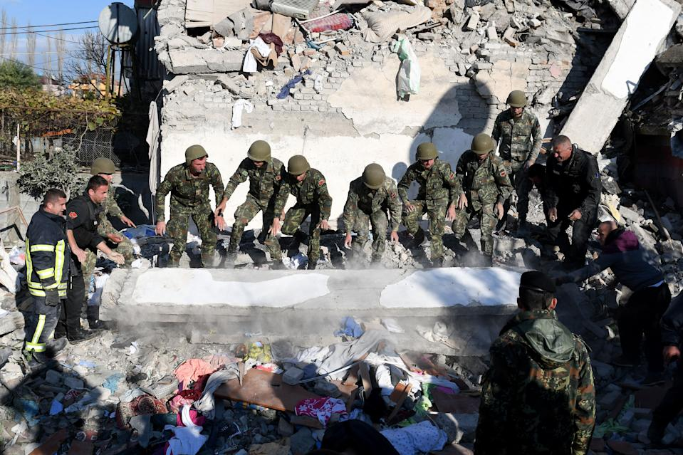 Emergency workers clear debris at a damaged building in Thumane, 34 kilometres (about 20 miles) northwest of capital Tirana, after an earthquake hit Albania, on November 26, 2019. Photo: Gent Shkullaku/AFP via Getty Images)