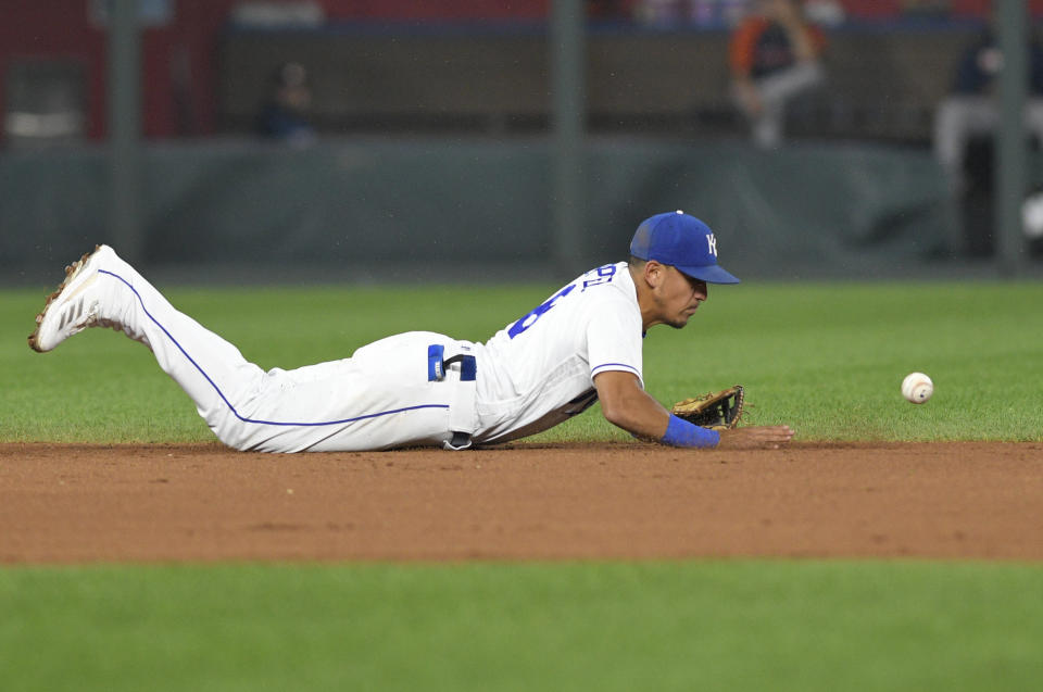Kansas City Royals shortstop Nicky Lopez knocks the ball down but can't make the throw to first on a single by Houston Astros' Gary Pettis during the fifth inning of a baseball game Tuesday, Aug. 17, 2021, in Kansas City, Mo. (AP Photo/Reed Hoffmann)