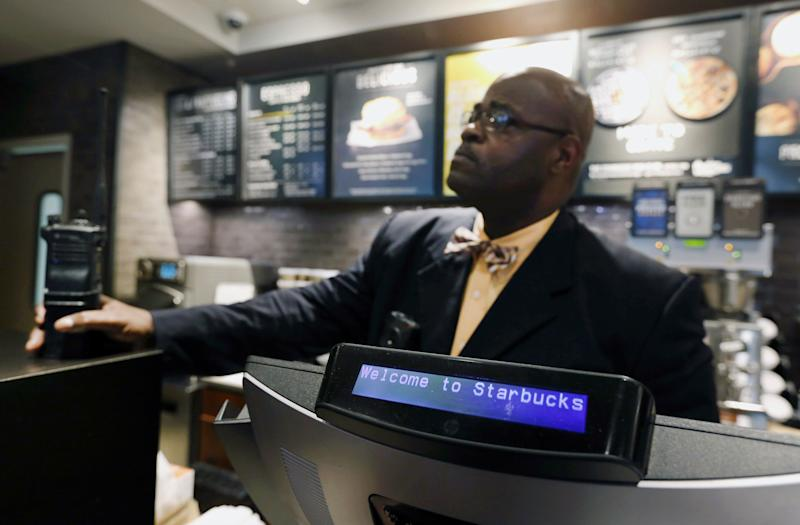 """A plain-clothed police officer mans a position behind the counter at the Starbucks that has become the center of protests in Monday, April 16, 2018, in Philadelphia. Starbucks wants to add training for store managers on """"unconscious bias,"""" CEO Kevin Johnson said Monday, as activists held more protests at a Philadelphia store where two black men were arrested after employees said they were trespassing. (AP Photo/Jacqueline Larma)"""
