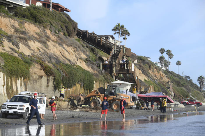 Search and rescue personnel work at the site of a cliff collapse at a popular beach Friday, Aug. 2, 2019, in Encinitas, Calif. At least one person was reportedly killed, and multiple people were injured, when an oceanfront bluff collapsed Friday at Grandview Beach in the Leucadia area of Encinitas, authorities said.(AP Photo/Denis Poroy)