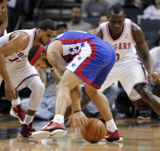 New Jersey Nets' Deron Williams, middle, recovers a loose ball as Charlotte Bobcats' D.J. Augustin, right, and Bismack Biyombo, left, are late to the ball in the first half of an NBA basketball game in Charlotte, N.C., Friday, March 9, 2012. (AP Photo/Bob Leverone)