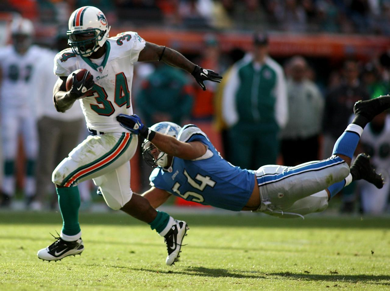 MIAMI - DECEMBER 26:  Running back Ricky Williams #34 of the Miami Dolphins breaks away from linebacker DeAndre Levy #54 of the Detroit Lions at Sun Life Stadium on December 26, 2010 in Miami, Florida. The Lions defeated the Dolphins 34-27.  (Photo by Marc Serota/Getty Images)
