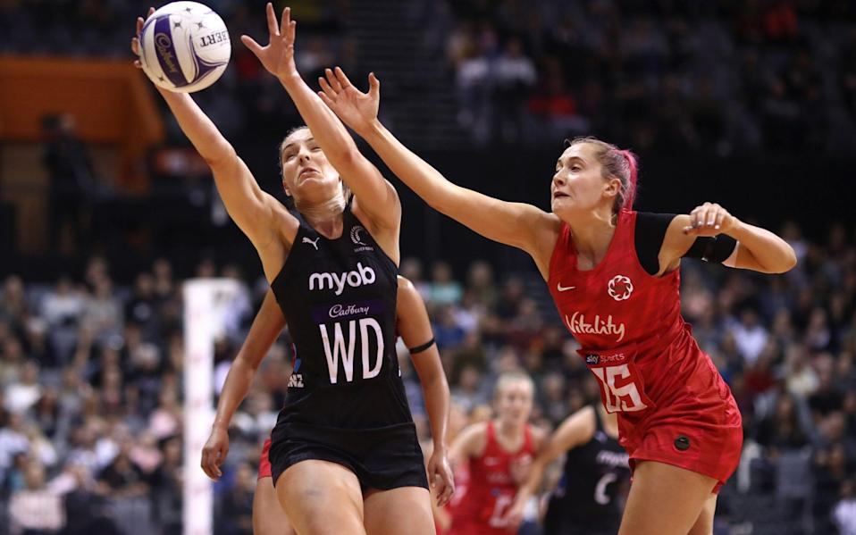 Karin Burger of New Zealand (left) takes a pass under pressure from England's George Fisher (right) - GETTY IMAGES