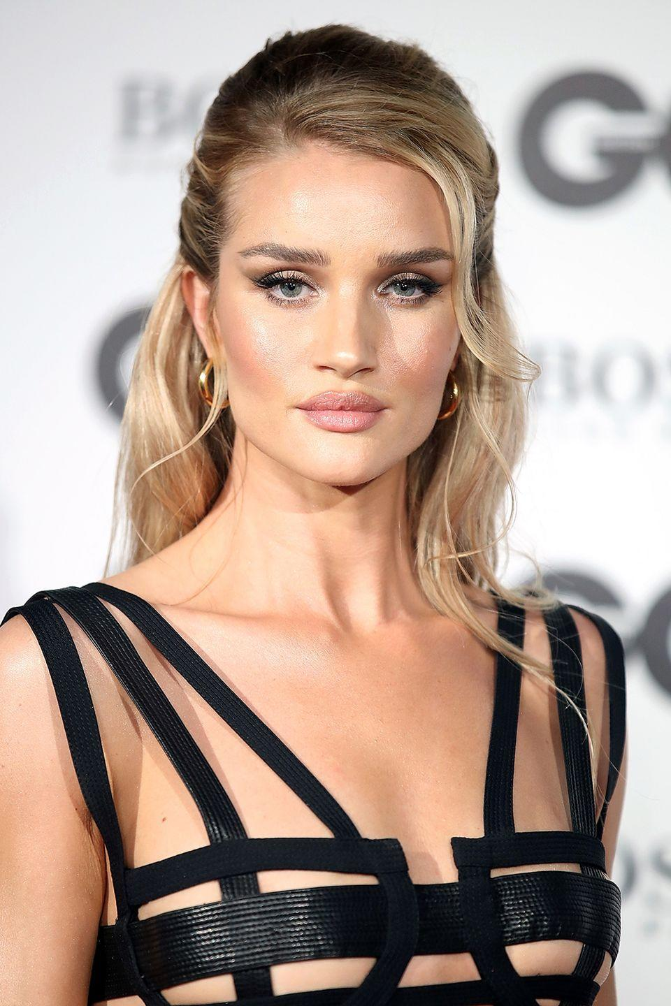 <p>Rosie Huntington-Whiteley's half-up hairstyle is neat and polished, save for a few wisps of hair framing her face for a more casual look. </p>