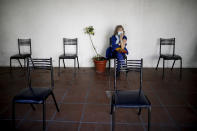 Carmela Corleto sits during an observation period after getting her first shot of the AstraZeneca vaccine for COVID-19 at a vaccination center in Almirante Brown, Argentina, Friday, April 23, 2021. (AP Photo/Natacha Pisarenko)