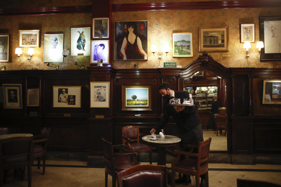A waiter clears a table at the Cafe Tortoni in Buenos Aires, Argentina, Tuesday, Nov. 10, 2020. With the end of the lockdown to avoid the spread of the new coronavirus, the traditional cafes of Buenos Aires, like the Tortoni, have begun to revive after seven months that plunged them into a crisis, representative of the paralysis that has caused the closure of thousands of small businesses in Argentina. (AP Photo/Natacha Pisarenko)