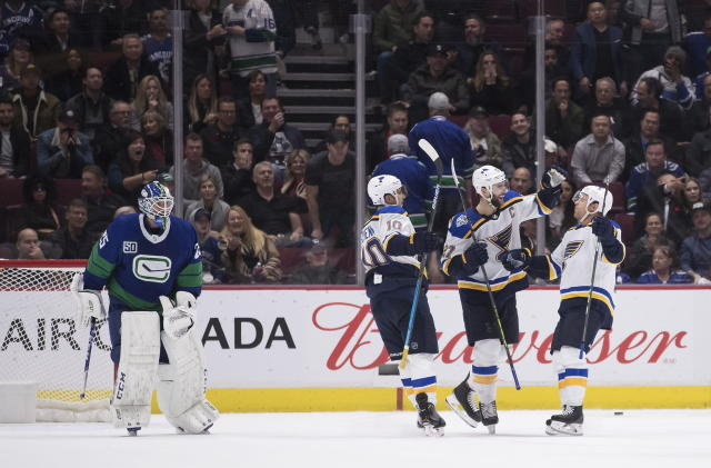 St. Louis Blues' Brayden Schenn, Alex Pietrangelo (27) and Jaden Schwartz, right, celebrate Schwartz's goal against Vancouver Canucks goalie Jacob Markstrom, of Sweden, during overtime in an NHL hockey game Tuesday, Nov. 5, 2019, in Vancouver, British Columbia. (Darryl Dyck/The Canadian Press via AP)