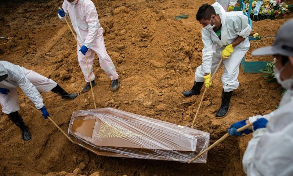 Workers lower the coffin of a Covid victim in Brazil