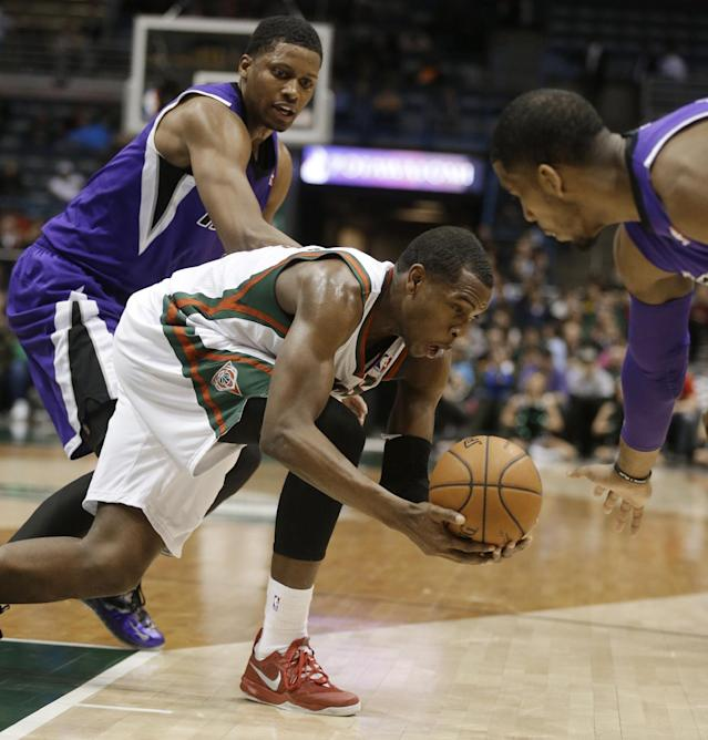 Milwaukee Bucks' Khris Middleton reaches for a loose ball ahead of Sacramento Kings' Rudy Gay, left, during the first half of an NBA basketball game Wednesday, March 5, 2014, in Milwaukee. (AP Photo/Jeffrey Phelps)