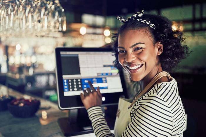 A young woman using a digital point-of-sale system.