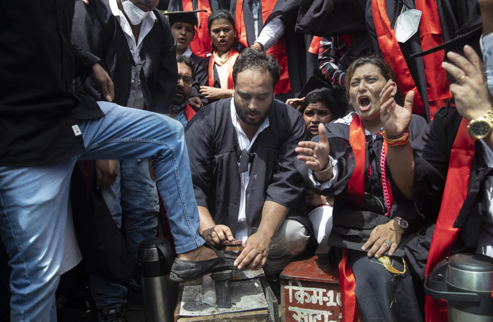 An Indian Youth Congress member polishes a shoe to symbolise unemployment, as he joins a protest where they marked Indian Prime Minister Narendra Modi's birthday as National Unemployment Day in Mumbai, India, Friday, Sept. 17, 2021. (AP Photo/Rafiq Maqbool)