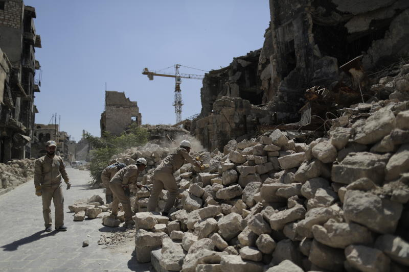 In this Saturday, July 27, 2019 photo, Syrian workers remove rubble from damaged shops in the old city of Aleppo, Syria. Much of Aleppo's centuries-old covered market is still in ruins but slowly small parts of it have been renovated where business is slowly coming back to normal nearly three years after major battles in Syria's largest city and once commercial center came to an end. (AP Photo/Hassan Ammar)