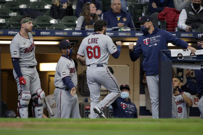Minnesota Twins' Jake Cave (60) is congratulated in the dugout after scoring from third base on a wild pitch during the third inning of an opening day baseball game against the Milwaukee Brewers on Thursday, April 1, 2021, in Milwaukee. (AP Photo/Aaron Gash)