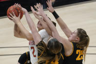 Maryland's Mimi Collins (2) puts up a shot against Iowa's McKenna Warnock (14) and Monika Czinano (25) during the first half of an NCAA college basketball game in the championship of the Big Ten Conference tournament, Saturday, March 13, 2021, in Indianapolis. (AP Photo/Darron Cummings)