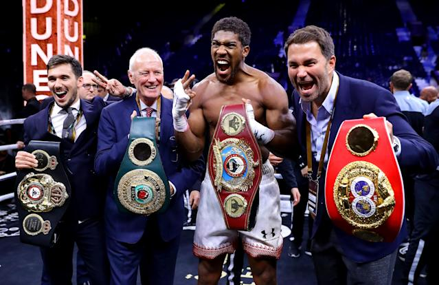 Anthony Joshua poses with Eddie Hearn (R) and Barry Hearn (second from left). (Photo by Richard Heathcote/Getty Images)
