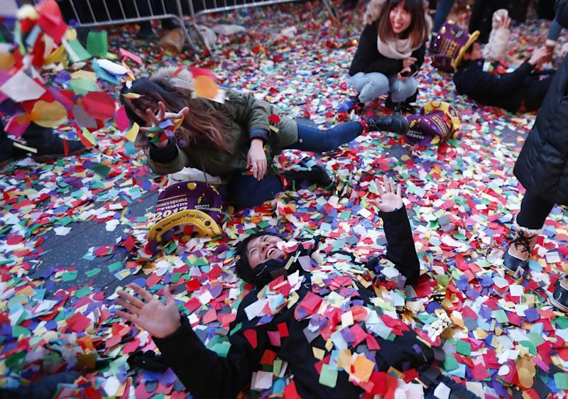 Revelers throw confetti on themselves after after celebrating the new year in Times Square, Sunday, Jan. 1, 2017, in New York. (AP Photo/Julio Cortez)