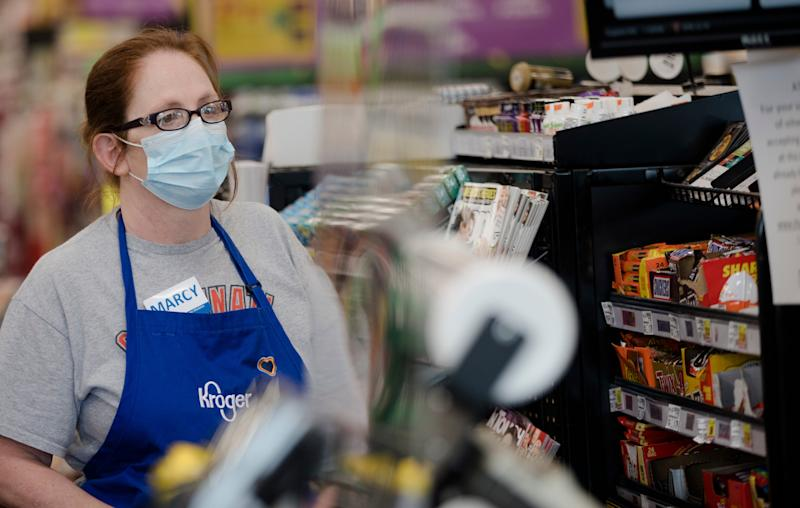 A Kroger employee wears a mask at Kroger on Tuesday, April 7, 2020, in Newport, Ky. Cleaning carts is one of the thing Kroger is doing to limit the spread of the new coronavirus.