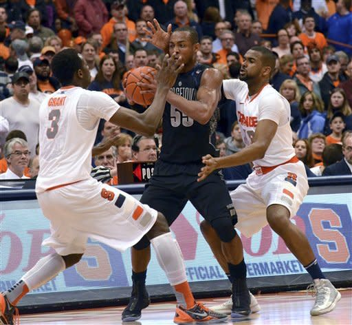 Georgetown's Jabril Trawick works between Syracuse's Jerami Grant, left, and James Southerland during the second half in an NCAA college basketball game in Syracuse, N.Y., Saturday, Feb. 23, 2013. Georgetown won 57-46. (AP Photo/Kevin Rivoli)