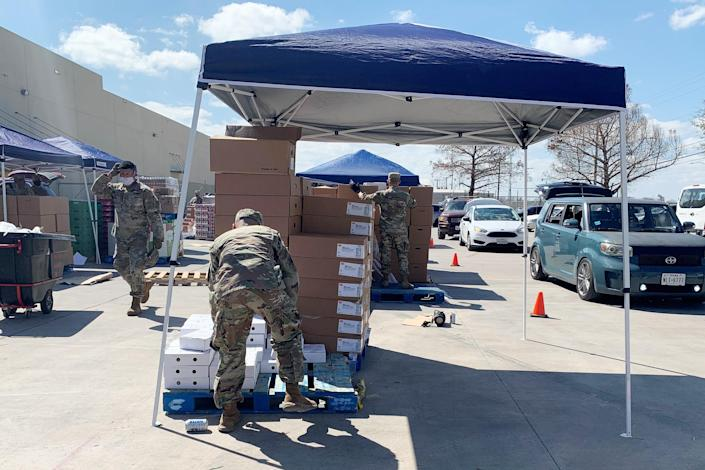 Texas National Guard members help load cars at the San Antonio Food Bank's afternoon distribution on Feb. 23, 2021. (Suzanne Gamboa / NBC News)