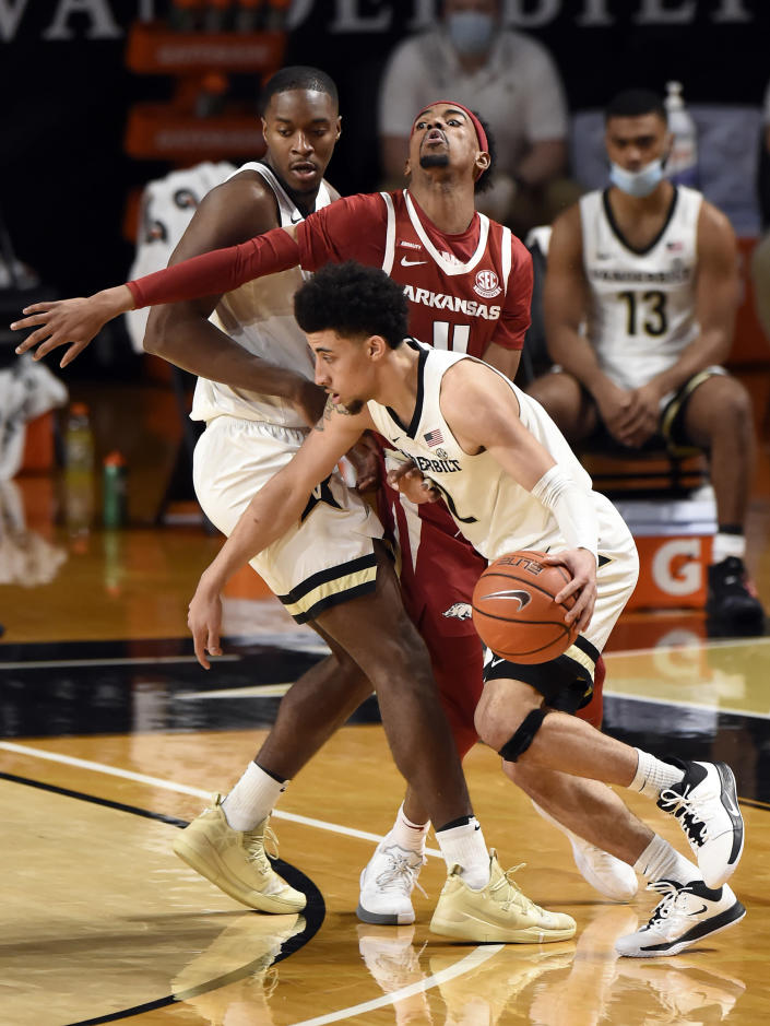 Vanderbilt guard Scotty Pippen Jr. (2) drives around Arkansas guard Jalen Tate (11) and as forward Clevon Brown, left, sets a pick during the second half of an NCAA college basketball game against Vanderbilt Saturday, Jan. 23, 2021, in Nashville, Tenn. Arkansas won 92-71. (AP Photo/Mark Zaleski)