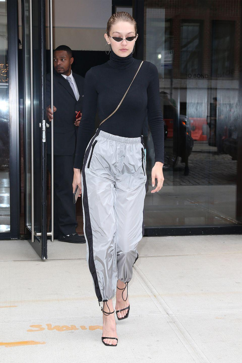<p>In a black turtleneck, gray sweat pants, heeled sandals, hoop earrings, and mini cat eyed sunglasses while out in New York.</p>