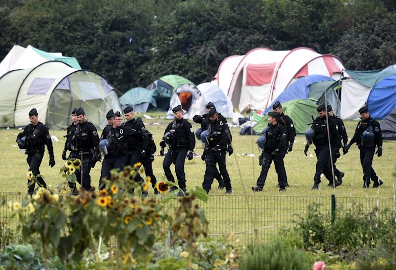French riot police walk by tents during the evacuation of the Grande-Synthe migrant camp