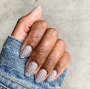 """Nothing says """"Jingle All the Way"""" like a festive splash of glitter to get you in the holiday mood. Make it <a href=""""https://oliveandjune.com/products/exclamation-point"""" rel=""""nofollow noopener"""" target=""""_blank"""" data-ylk=""""slk:Olive & June's Exclamation Point"""" class=""""link rapid-noclick-resp"""">Olive & June's Exclamation Point</a> (seen here) that has the perfect mix of holographic sparkles."""