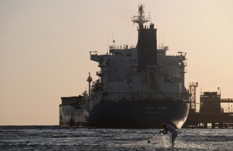 Fisherman pulls in his net as an oil tanker is seen at the port in the northwestern city of Duba