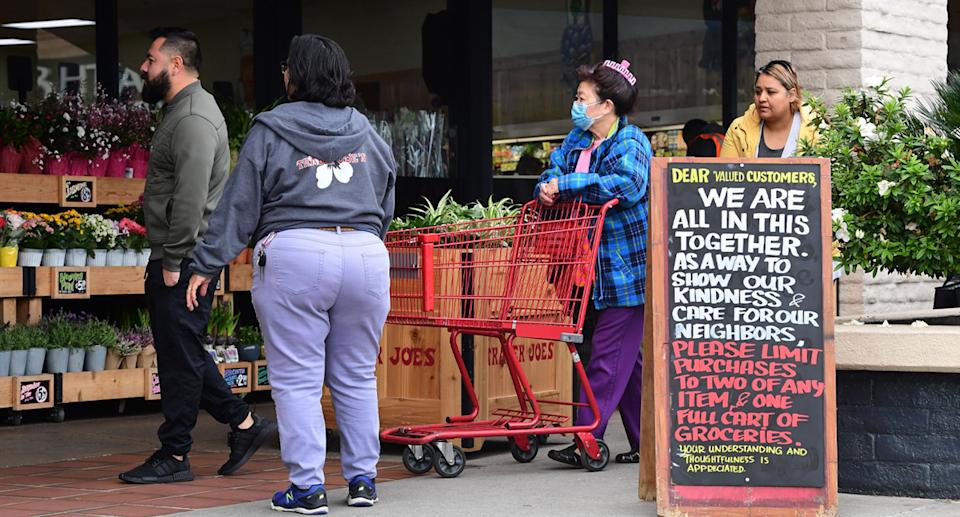 Shoppers, some without face masks, outside a Trader Joe's supermarket in the US.