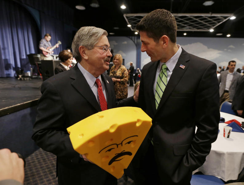 FILE - In this Nov. 16, 2013 photo, U.S. Rep. Paul Ryan, R-Wisc., talks with Iowa Gov. Terry Branstad, left, after presenting him with a cheesehead hat during Branstad's birthday bash and fundraiser in Altoona, Iowa. Branstad talked privately with Ryan before the fundraiser about a proposed reduction in the minimum amount of ethanol in the nation's fuel supply. (AP Photo/Charlie Neibergall, File)