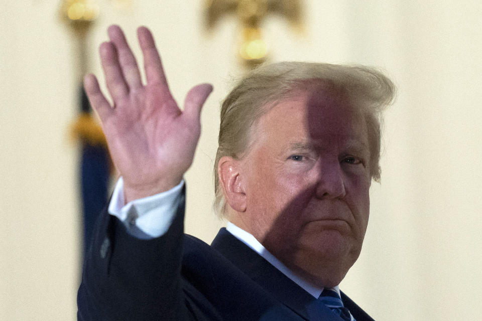 President Donald Trump waves from the Blue Room Balcony upon returning to the White House Monday, Oct. 5, 2020, in Washington, after leaving Walter Reed National Military Medical Center, in Bethesda, Md. Trump announced he tested positive for COVID-19 on Oct. 2. (AP Photo/Alex Brandon)