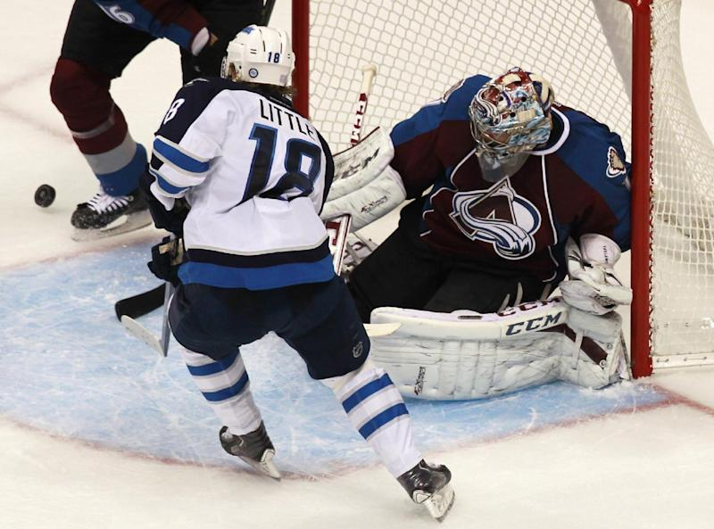Colorado Avalanche goalie Semyon Varlamov, back, of Russia, deflects a shot off the stick of Winnipeg Jets center Bryan Little in the third period of the Avalanche's 3-2 victory in an NHL hockey game in Denver on Sunday, Oct. 27, 2013. (AP Photo/David Zalubowski)
