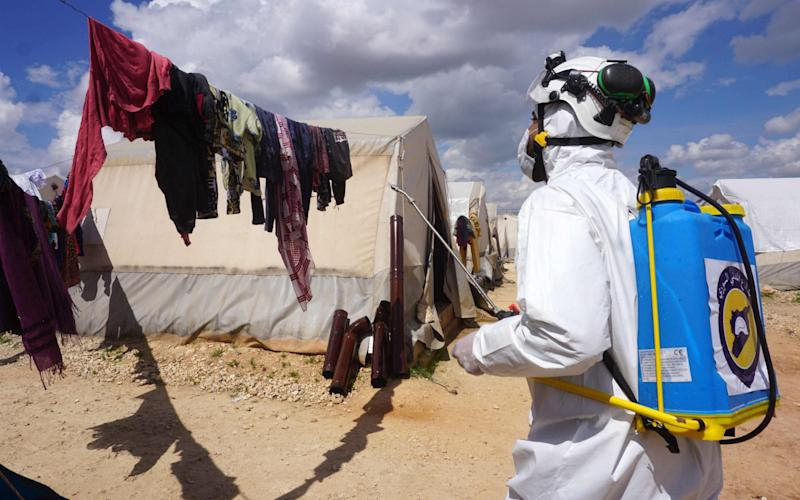 A member of the Syrian civil defence, also known as the White Helmets, sprays disinfectant on washing hanging outside a tent - MUHAMMAD HAJ KADOUR / AFP
