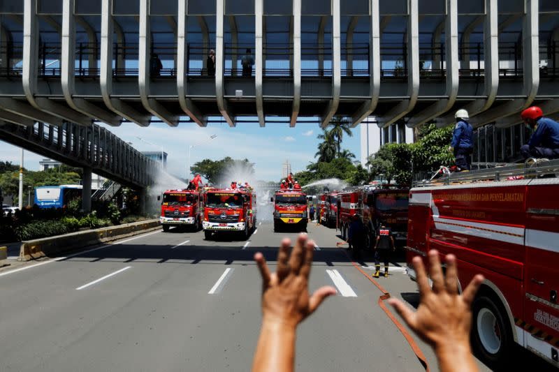 A firefighter gestures to fellow firefighters to stop spraying disinfectant in order to refill their tanks, as the disinfectant is integral in the prevention of the spread of the coronavirus disease (COVID-19), on the main road in Jakarta
