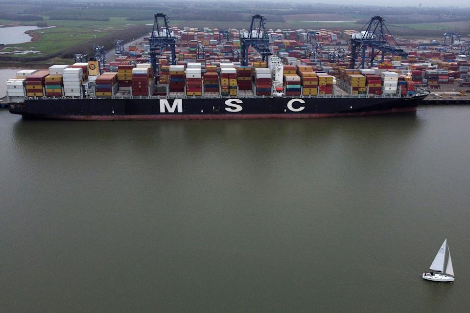 "An aerial view shows a sail boat passing Container ship MSC Maria Saveria docked in the port of Felixstowe, east of London on December 12, 2020. - Food shortages, tailbacks and congested ports: as talks with Brussels remain unresolved three weeks before leaving the EU single market, the UK is preparing for a chaotic ""no-deal"". (Photo by BEN STANSALL / AFP) (Photo by BEN STANSALL/AFP via Getty Images)"