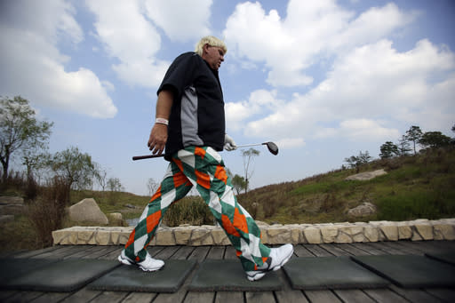 John Daly of the U.S. walks toward to the 3rd hole during a pro-am competition ahead of the BMW Masters golf tournament at the Lake Malaren Golf Club in Shanghai, China, Wednesday, Oct. 23, 2013. The European Tour event will begin on Oct. 24. (AP Photo/Eugene Hoshiko)