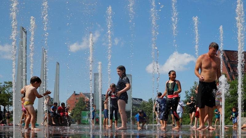 A photograph of kids and adults cooling off in a fountain.